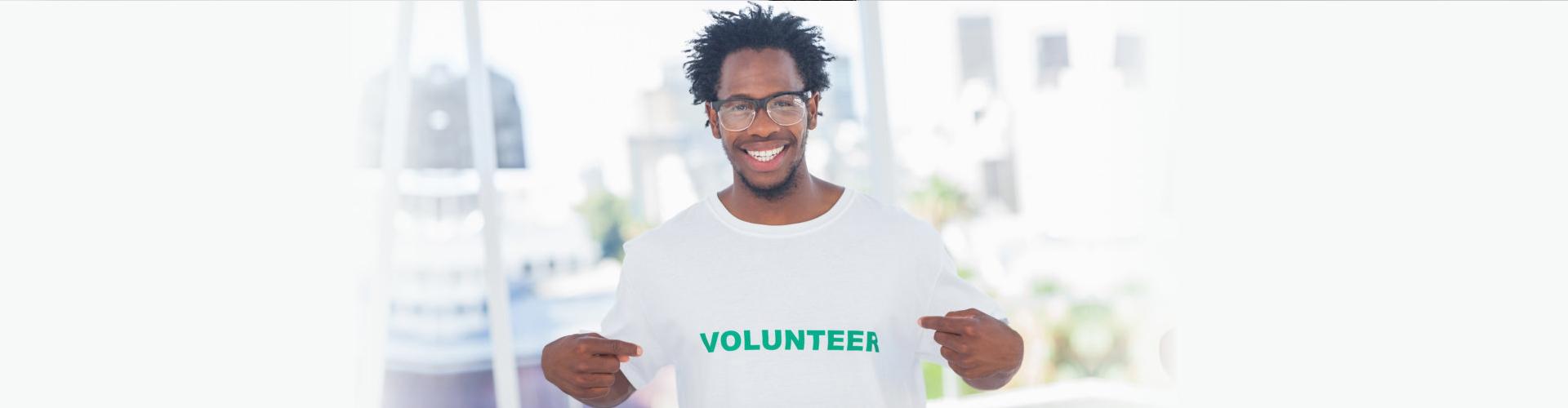 young man wearing volunteer shirt smiling